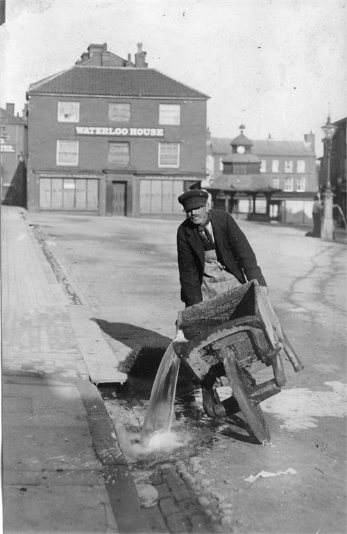 Photograph. Bruff Hewitt flushing the surface drains in the North Walsham Market Place (North Walsham Archive).