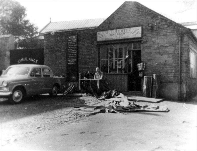 Photograph. Jack Hewitt outside his Saddler's Shop on Church Plain North Walsham (North Walsham Archive).