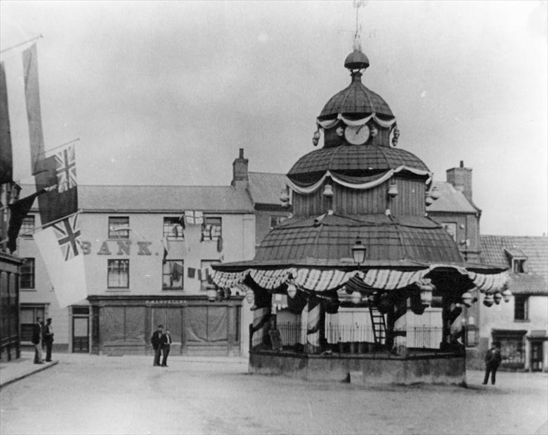 Photograph. Market Cross, North Walsham, decorated for Queen Victoria's Diamond Jubillee, 1897 (North Walsham Archive).