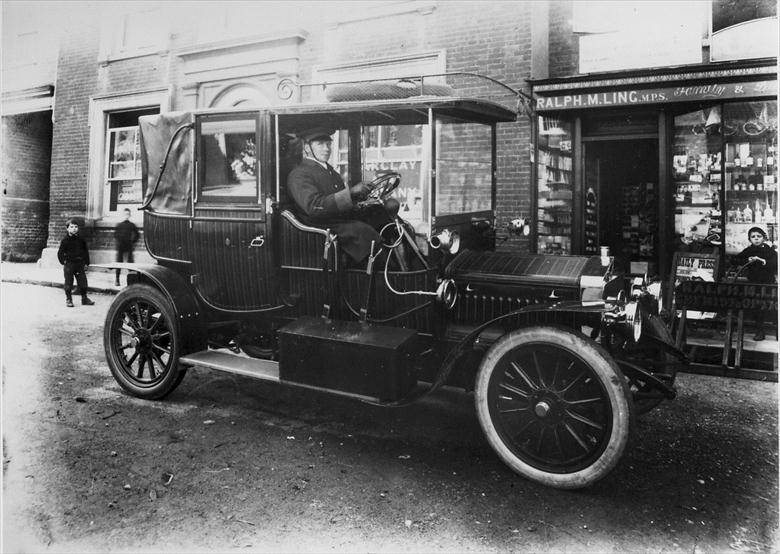 Photograph. Mrs Berney Petres' car in North Walsham Market Place 1909. The chaufeur is Mr Henry Thomas Thurling (North Walsham Archive).