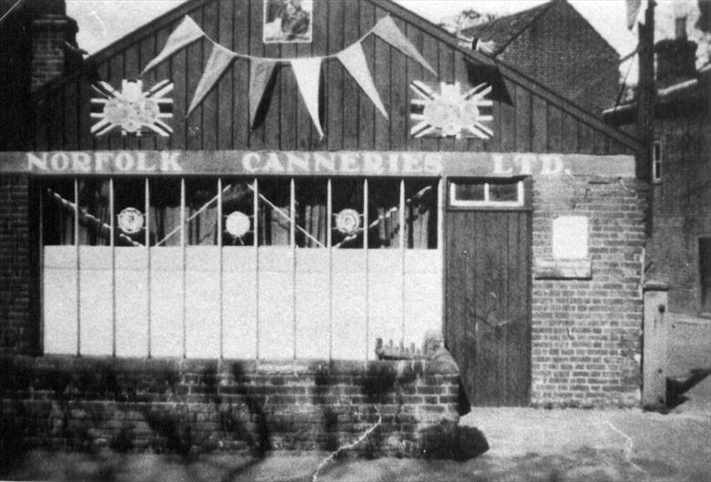 Photograph. Norfolk Canneries Ltd., Park Hall, New road, North Walsham. Decorated to celebrate the 1937 Coronation of King George VI and Queen Elizabeth. (North Walsham Archive).