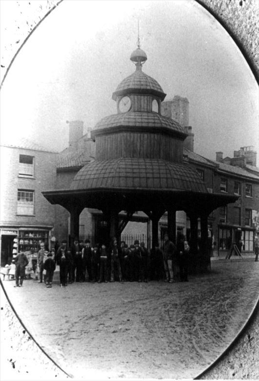Photograph. North Walsham Market Cross, c1880's. Dyball, Earthenware Dealer on left....sold shop to Stead & Simpson's around 1890. (North Walsham Archive).