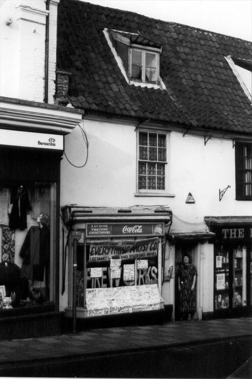 "Photograph. Pam Palmer at the door of the ""Yellow Shop"", a confectioners at 26 Market Place, North Walsham. Opened 1965, Closed Nov. 2000. Photo:-R.M.Ling.(11) (North Walsham Archive)."
